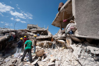 Workers dig through the rubble of KOTELAM, a credit union in Port-au-Prince.