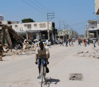 Man rides bicycle through devastated Haiti streets.