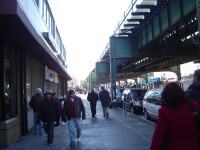 Well-known Roosevelt Avenue, the bustling commercial and cultural center of Corona, New York. In the background, New York's elevated metro line number 7 parallels Roosevelt while Spanish is heard on the streets below.