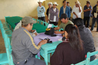 Other group members wait patiently as each member takes their turn meeting with the rural financial officers to deposit their savings and verify their account balance. Each member receives a record of the transaction printed on a small handheld printer.