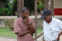 Gideon Nyamwange (right), former senior deputy commissioner of cooperatives in Kenya and one of WOCCU's consultants working on the Tanzania program, converses with an employee at a SACCOS training center in Dar es Salaam.