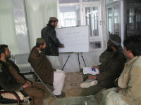 A Greshk IIFC Membership Development Officer explains the IIFC's financial products to a group of new members in Helmand province.