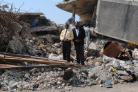 KOTELAM Chairman Jean Hubert Lindor (left) and Director Gervase Michel stand atop the rubble that was once the Magloire Ambroise branch in downtown Port-au-Prince.