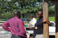 Susan Nduati, marketing specialist for the WOCCU-USDA program in Kenya, talks with fellow colleague, John Inganga, at the Finlays estates in Kericho, Kenya. Susan has worked closely with John and the rest of WOCCU's agriculture team to identify proper crops and markets for farmers, caregiver groups and people living with HIV/AIDS.