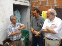 Juan Manuel Sanchez demonstrates the sandal production process to Oscar de Leon and Brian Branch.