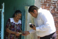 A credit union representative (right) conducts a transaction with a member in rural Mexico using new handheld technology now part of WOCCU's semilla cooperativa program.