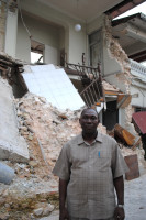 Haitian credit union chair stands beside wrecked building