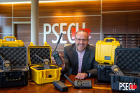 PSECU President George Rudolph poses with several of the 25 satellite phones donated to World Council.